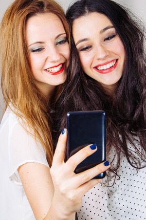 smug: Funny girl friends taking selfies with a mobile