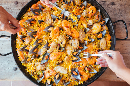 spanish food: Mixed paella and hands with forks taking rice. Aerial view.