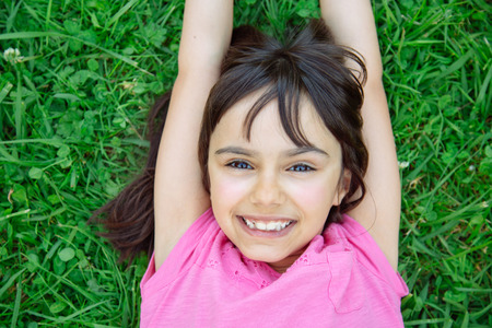 6 years girl: Cute little girl lying in the grass smiling Stock Photo