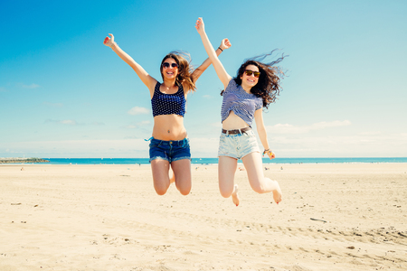 girl in shorts: Happy and funny girl friends jumping on the beach, Some blur on legs beacuse of movement Stock Photo
