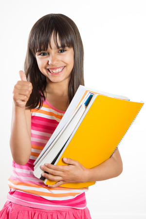 Cute young and happy school girl holding books showing thumbs up