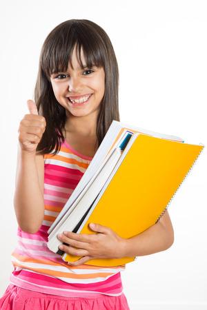 Schattig jong en gelukkig school meisje met boeken blijkt thumbs up