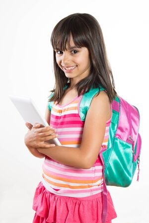 Cute and happy young school girl with schoolbag holding a tablet. Isolated on white