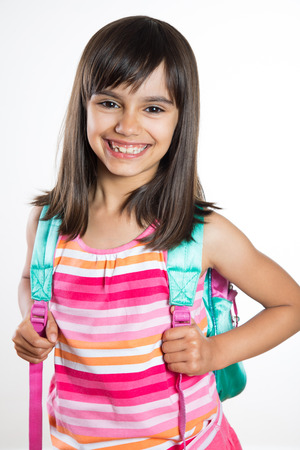 Portrait of a young and happy school girl holding a schoolbag. Isolated on white