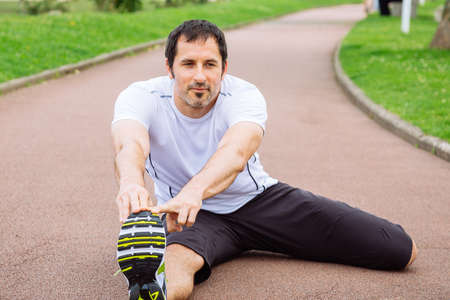 mid adult: Attractive mid adult spotrsman doing stretching exercises outdoors in a track
