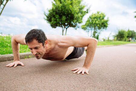mid adult man: Mediados de hombre adulto haciendo flexiones al aire libre sin camisa Foto de archivo