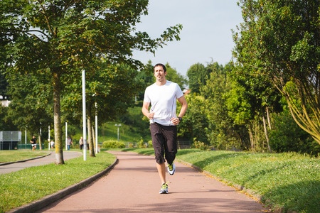 Man running on a track in a sunny day