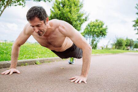 pushups: Mid adult man doing pushups outdoors shirtless Stock Photo