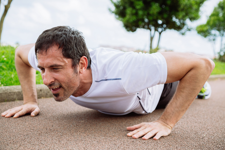pushups: Mid adult man doing pushups outdoors