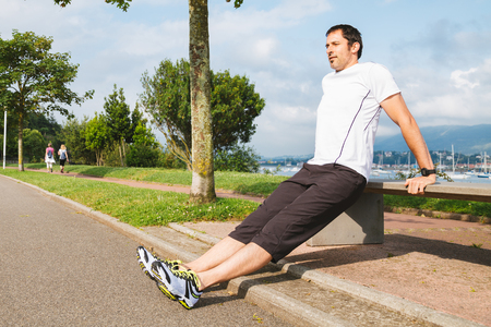 mid adult: Mid adult man doing pushups outdoors using a bench