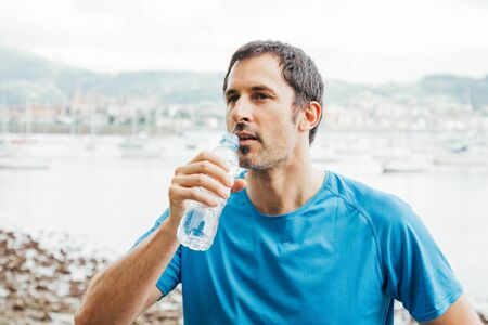 man drinking water: Running man drinking water after trainning Stock Photo