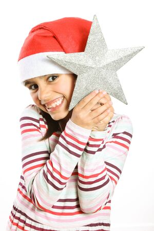 holding a christmas ornament: Funny and cute little girl with Santa hat holding a Christmas tree star smiling