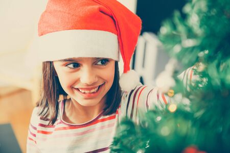 decorating christmas tree: Cute and happy little girl with Santa hat decorating the Christmas tree at home. Filter effect added. Stock Photo
