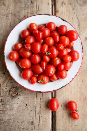 aereal: Natural ripe tomate cherry in a rustic dish and table. Aereal view.