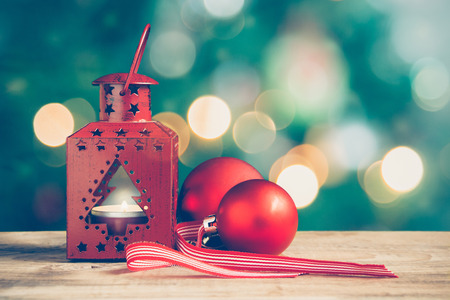 Red Christmas lantern and balls on a wooden table. Christmas tree and lights at the background.