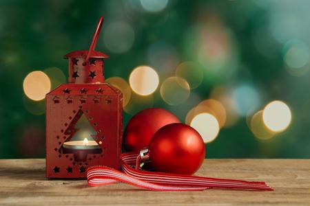 나무 테이블에 레드 크리스마스 랜 턴과 공. 배경에서 크리스마스 트리와 조명.