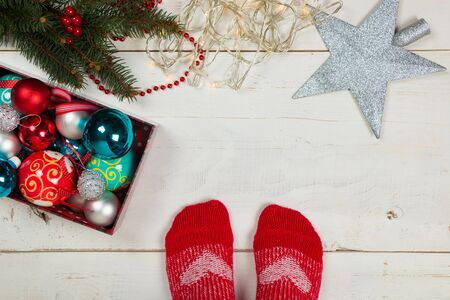 decorating: Feet of a person with red socks ready for decorating the Christmas tree surrounded by various ornaments on the floor Stock Photo