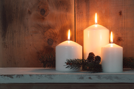 Christmas candles and fir branches over wooden background