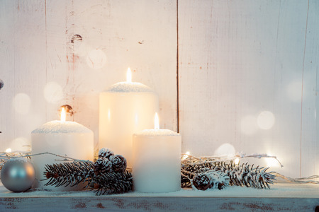 Christmas candles and snowy fir branches over white wooden background with lights Stock Photo