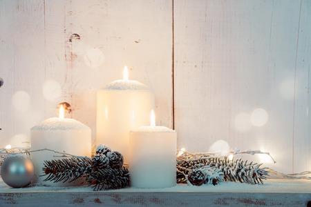 Kerst kaarsen en besneeuwde dennentakken op een witte houten achtergrond met verlichting