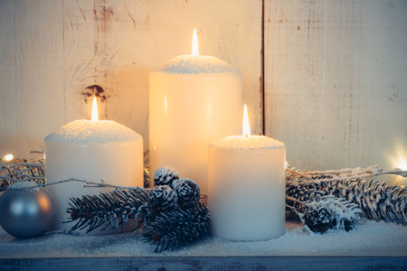christmas gold: Christmas candles and snowy fir branches over white wooden background with lights Stock Photo