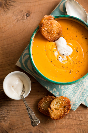 Pumpkin soup in a bowl with coconut cream and fried bread croutons with sesame