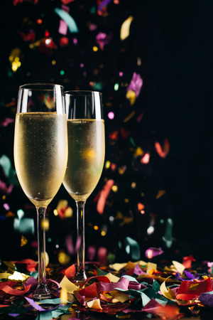 Two bright icy champagne glasses and confetti falling