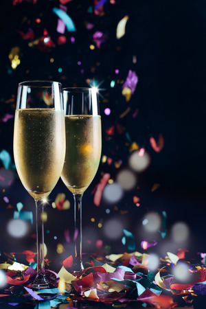 Two bright icy champagne glasses and confetti falling Imagens - 47071066