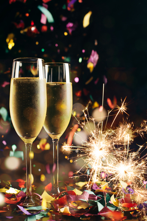 Two bright icy champagne glasses, confetti falling and sparklers