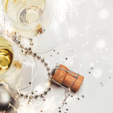 feestelijk: Twee glazen champagne en kurk met kerstballen, sterretjes, confetti en verlichting. Kopieer ruimte. Stockfoto