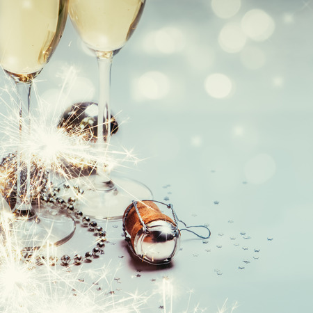 Two champagne glasses and cork with baubles, sparklers, confetti and lights. Copy space. Stockfoto