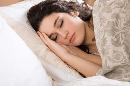 dormir: Mujer morena joven que duerme en la cama cubierta con una colcha floreada de color beige Foto de archivo