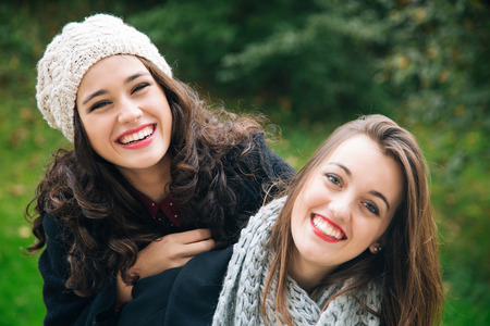 friends hugging: Cute best friend girls a piggyback in winter or fall outdoors