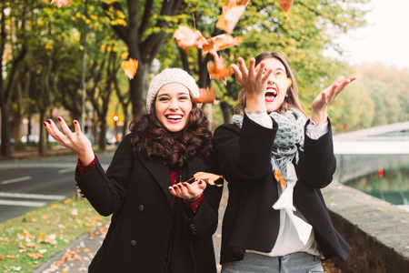 가을에 도시의 마른 나뭇잎을 던지는 재미 있은 여자 친구