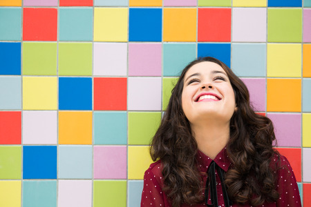 Happy girl laughing against a colorful tiles background. Concept of joy Фото со стока