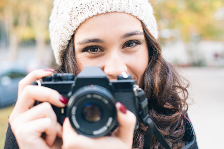Portrait of a young beautiful woman with an analog camera in autumn looking to you 写真素材