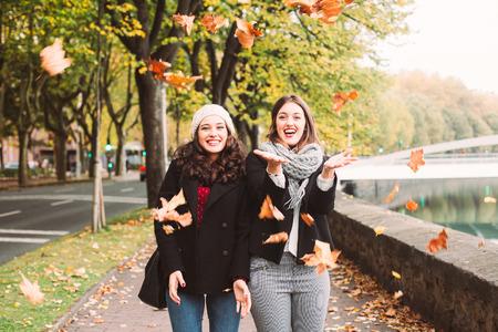 mooie vrouwen: Grappig meisje vrienden gooien van droge bladeren in de stad in de herfst