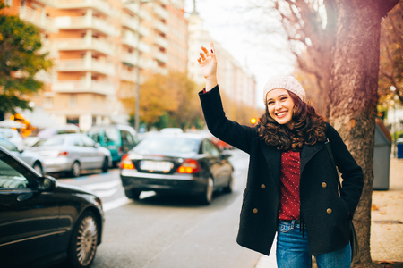 city road: Happy young beautiful woman calling for a taxi with arm raised in the city in autumn