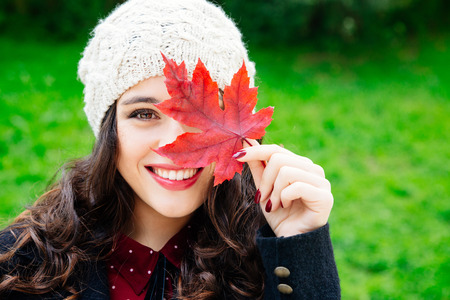 Beautiful young woman with woolen cap covering face with a red leaf while smiling against a green background. Fresh skin and healthy smile.