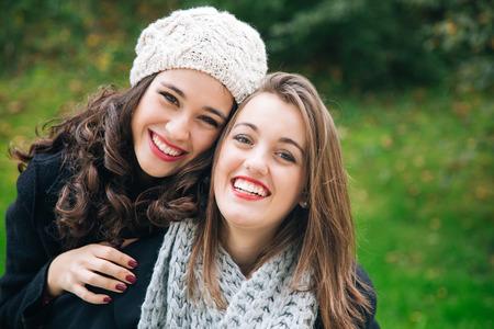 niñas sonriendo: Lindo mejores amigo de las niñas a cuestas en invierno al aire libre