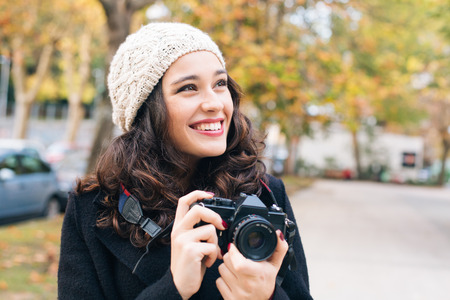 Happy young beautiful woman with an analog camera capturing autumn in the city