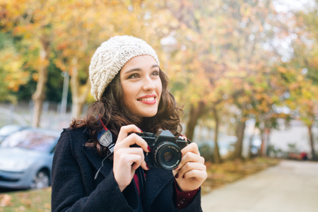 capturing: Happy young beautiful woman with an analog camera capturing autumn in the city