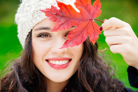 fall beauty: Beautiful young woman with woolen cap covering face with a red leaf while smiling against a green background. Fresh skin and healthy smile.