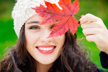 Schöne junge Frau mit Wollmütze für das Gesicht mit einem roten Blatt, während lächelnd vor einem grünen Hintergrund. Frische Haut und gesundes Lächeln. Standard-Bild