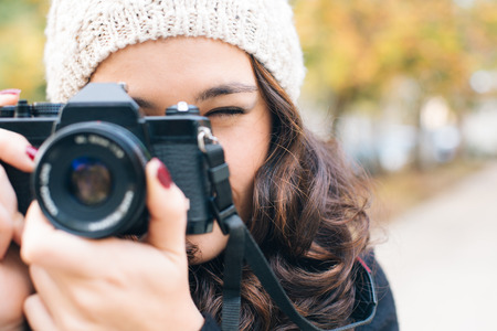 camera: Close up of a young beautiful woman with an analog camera shooting to you in autumn