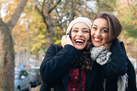 Laughing best friends hugging outdoors in autumn