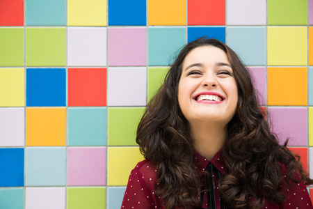 happiness: Feliz niña riendo contra un fondo de los azulejos de colores. Concepto de la alegría Foto de archivo