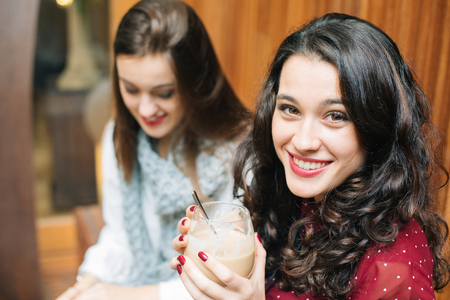 Beautiful young woman having a coffee with a friend looking at camera