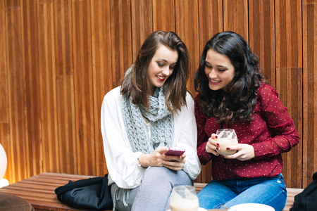 Two beautiful young women using a mobile phone while having a coffee in a cafe