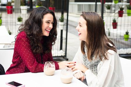 mujeres juntas: Mujeres lindas jóvenes que ríen mientras toma un café al aire libre Foto de archivo